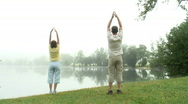 Couple doing gymnastics at a lake Stock Footage