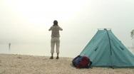 Woman with binocular beside tent at mountain lake Stock Footage