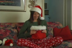 Beautiful Brunette Pulls a Suprise From Her Christmas Bag Stock Footage