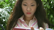 Attractive young asian woman writes. Stock Footage