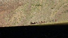 Horsemen and pack horses on mountain Stock Footage
