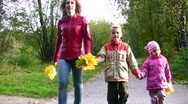Mother with children walking in autumn park Stock Footage