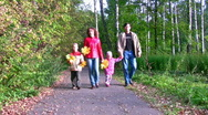 Family of four walking in autumn park Stock Footage