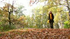 Woman in autumn park walking Stock Footage