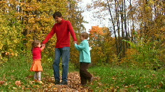 Father rotate two children in autumn park Stock Footage