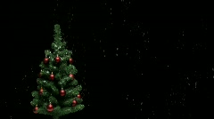 Snow falling on Christmas tree with red decorations Stock Footage