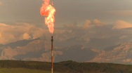 Oil & gas, Gas flare with mountains in background Stock Footage
