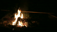Shadowy man putting more wood on campfire  Stock Footage