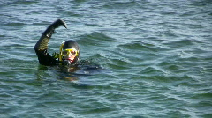 Scuba diver preparing a dive, diving, and surfacing Stock Footage