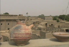 Djenne Roofs with jug Stock Footage