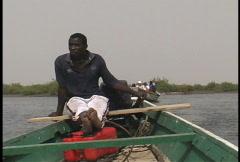 Boatman on a river in Senegal Stock Footage