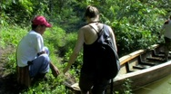 Woman getting onto jungle boat Stock Footage
