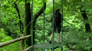 Woman walking across jungle bridge 2 Stock Footage