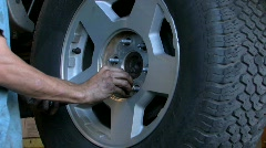 Mechanic replacing lug nuts on vehicle wheel Stock Footage