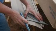 Carpenter measuring aluminum siding Stock Footage