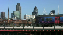 Commuter train on Blackfriars Bridge with the city office tower blocks in London - stock footage