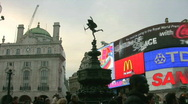 Stock Video Footage of Eros and brightly lit advertisements at dusk in Piccadilly Circus London England