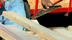 Carpenter measuring and sawing stud Stock Footage