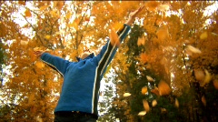Boy throws leaves up into air dolly shot 50% slowmo Stock Footage