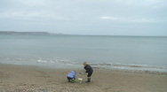 Children Playing on Weymouth Beach on Overcast Day Stock Footage