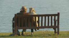 Elderly couple sitting on cliff in Weymouth - stock footage