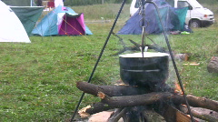 Preparing food in pot above bonfire 3  Stock Footage