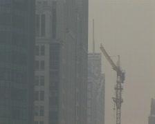Cranes constructing buildings under pollution Stock Footage