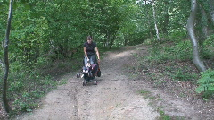 Young mother pushing daughter in pushchair through woods Stock Footage