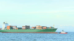 Container ship escorted by a tug Stock Footage