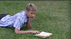 teenager lays on a grass and reads the book. - stock footage