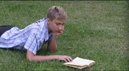 Stock Video Footage of teenager lays on a grass and reads the book.
