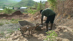 Malawi: african man fills the barrow with sand Stock Footage