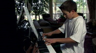 Practicing the piano full view Stock Footage