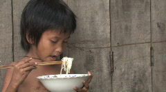 Poor Boy eats Rice Noodles - stock footage