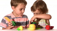 Stock Video Footage of brother with sister with plastic fruits
