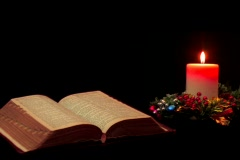 Open Bible by candle light and Christmas decorations Stock Footage