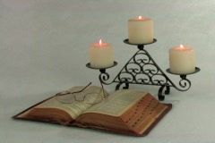 Open Bible in candelabra candle light - stock footage
