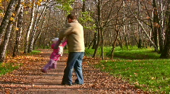 Grandfather rotate child in autumn park Stock Footage