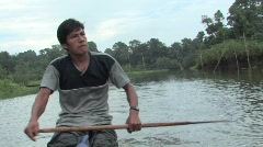 Amazon man paddling dugout canoe - stock footage