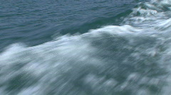 Splashing water and waves behind boat at sea - stock footage