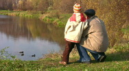 Stock Video Footage of senior with child. Ducks on pond.