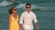 Couple walks along beach Stock Footage