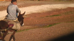 Kid on a donkey rural maroc africa Stock Footage