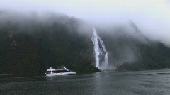Milford Sound boat passes falls - stock footage