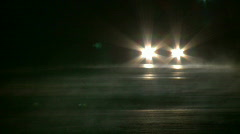 Car Headlights appear over hill on steamy road Stock Footage
