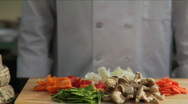 Chef adds Asian vegetables to wok Stock Footage