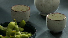 Man pours sake next to edamame Stock Footage