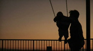 Father pushing son on swing at park at sunset Stock Footage