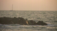 Sailboat in the sunset with rocks Stock Footage