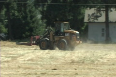 Tractor gathering hay bales Stock Footage